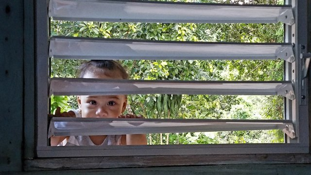 a toddler peers through slats in a window to see visitors to her rural Dominican Republic home