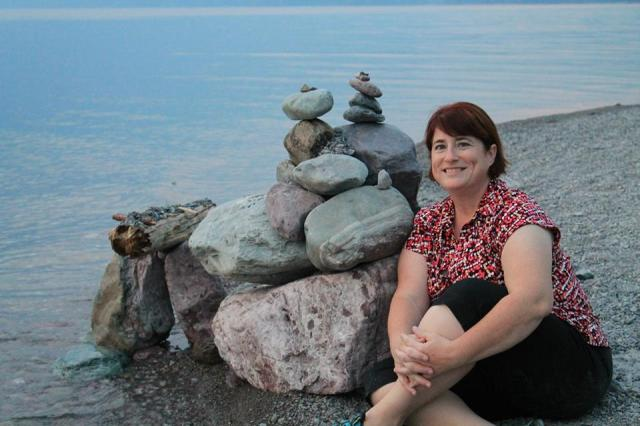 Kate Vanskike sitting by a cairn of rocks on the shores of Lake McDonald