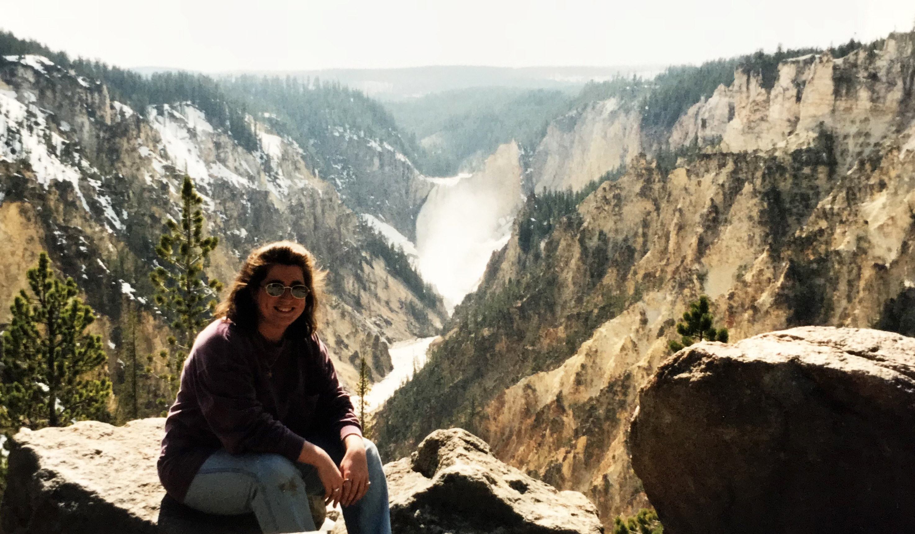 writer Kate Vanskike atop a mountain looking over the Grand Canyon of Yellowstone, Yellowstone National Park