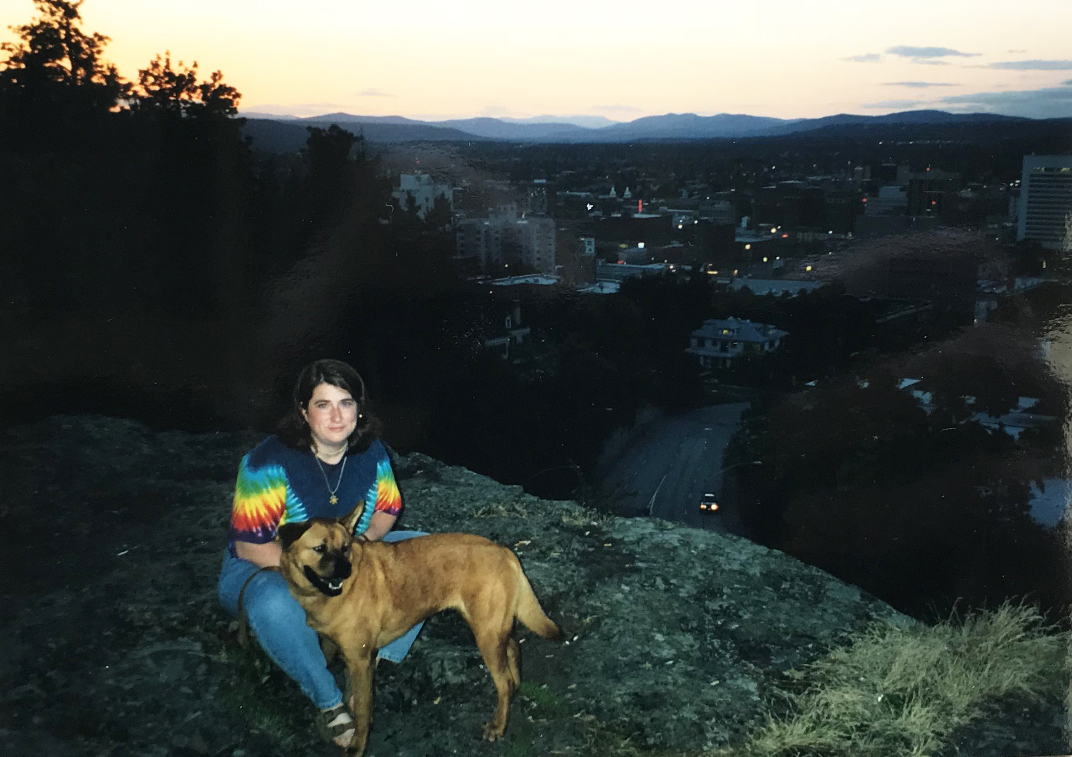 writer Kate Vanskike with her dog on a rock overlooking Spokane Washington